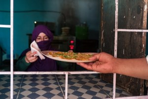 A customer picks up his camel pizza from a pizzeria in Awserd Credit: MEE/Eugenio G. Delgado