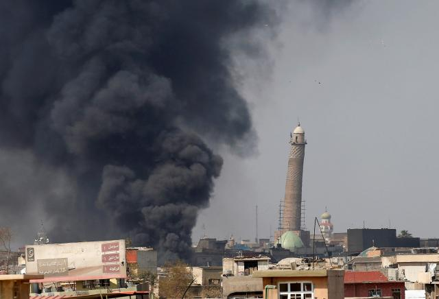 Smoke rises from clashes near Mosul's Al-Habda minaret at the Grand Mosque, March 17, 2017. Islamic State's black flag had been flying over its 150-foot (45-meter) leaning minaret since June 2014. Credit; Reuters/Youssef Boudlal