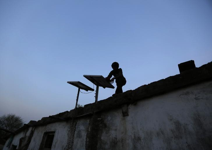 A boy dusts off a solar panel installed on the rooftop of his house on the outskirts of Ahmedabad October 27, 2014. Credit: Reuters/Amit Dave/Files