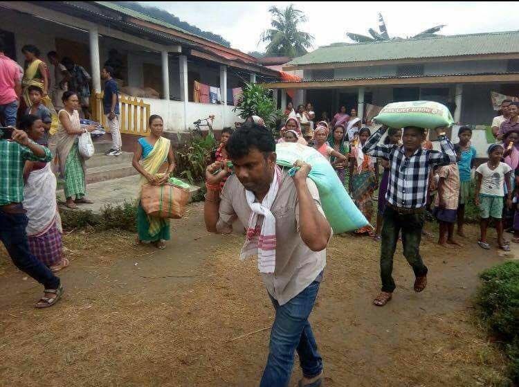 Congress MLA Rupjyoti Kurmi seen carrying relief material. Credit: Twitter