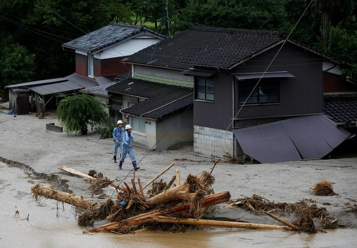 Men walk in front of damaged houses surrounded by swept away after heavy rain in Asakura, Fukuoka Prefecture, Japan July 9, 2017. Credit: Reuters/Issei Kato