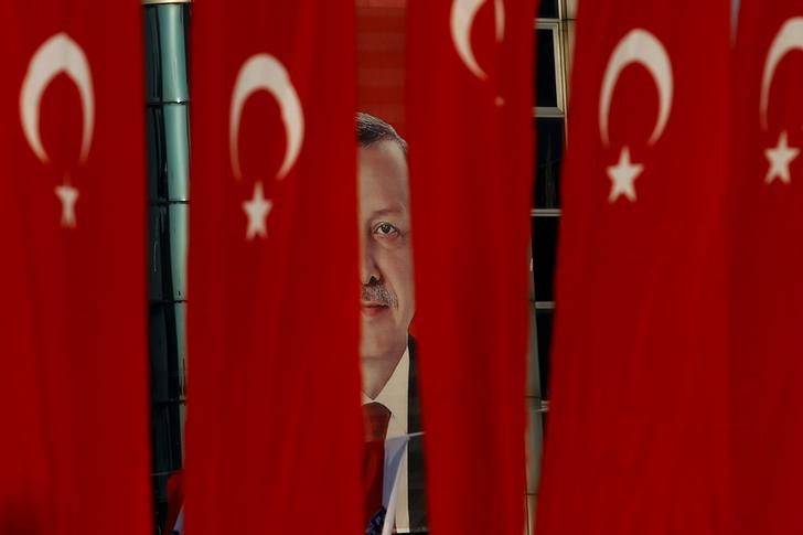 A picture of Turkish President Tayyip Erdogan is seen through Turkish national flags ahead of the constitutional referendum in Istanbul, Turkey, April 14, 2017. Credit: Reuters/Alkis Konstantinidis