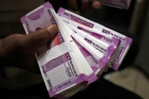 A cashier displays the new 2000 Indian rupee banknotes inside a bank in Jammu, November 15, 2016. Credit: Reuters/Mukesh Gupta