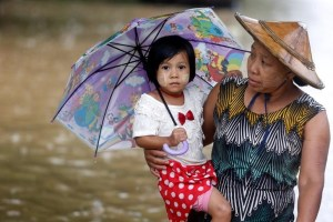 A woman carries her daughter as she walks on a flooded street in Kyaikto township, Mon state, Myanmar July 22, 2017. Credit: Reuters/Soe Zeya Tun