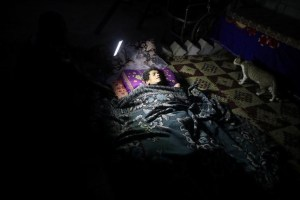 A disabled Palestinian woman lies on a mattress, as her relative holds a torch to show her to the photographer during a power cut in Khan Younis in the southern Gaza Strip, July 3, 2017. Credit: Reuters/Mohammed Salem