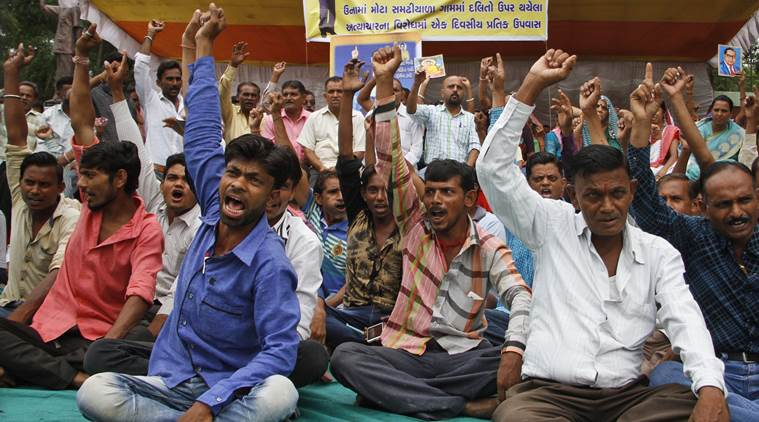 Members of India's low-caste Dalit community shouts slogans during a sit in protest against the alleged attack on their community members for skinning a dead cow in Una, in Ahmadabad, India, Friday, July 22, 2016. Videos of the four men being stripped and beaten with sticks by men claiming to be cow protectors in Gujarat state have gone viral and have sparked protests by Dalit groups across the state. Credit: PTI