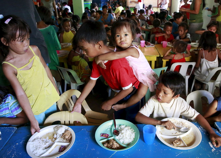Children eat free meals distributed by group World Mission Community Care in a slum in Manila. Credit: Reuters/Romeo Ranoco