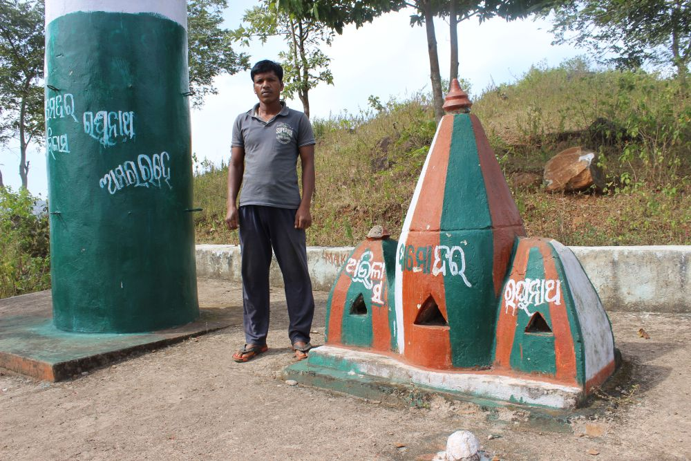 Subhas Jhodia standing near the tombstones of Abhilash Jhodia, Damodar Jhodia and Raghunath Jhodia, the three killed in police firing during a peaceful dharna against mining at Maikanch, Kashipur. Subhas is the younger brother of Abhilash. Credit: Abhijit Mohanty