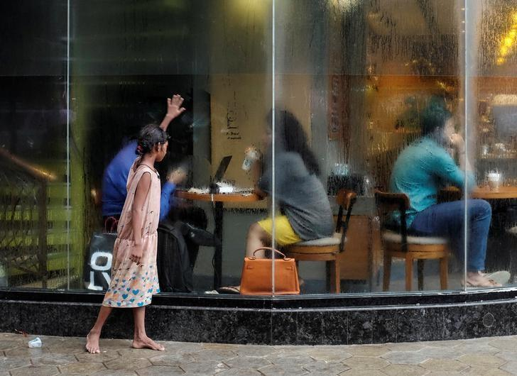 A homeless girl asks for alms outside a coffee shop in Mumbai, India, June 24, 2016. Credit: Reuters/Danish Siddiqui/Files