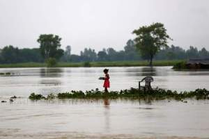 A girl carrying dishes walks along a flooded area in Janakpur, Nepal, August 13, 2017. Credit: Reuters/Navesh Chitrakar