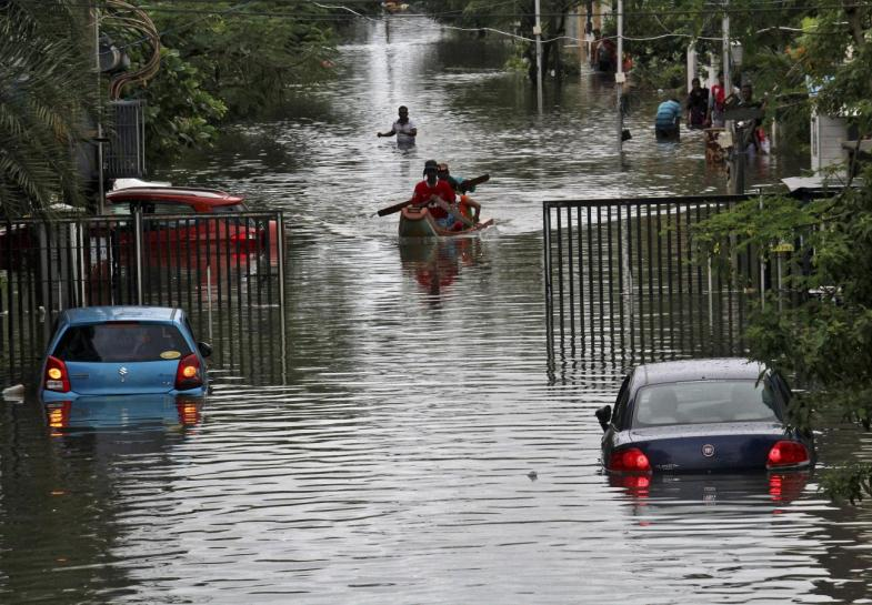 People travel on a boat as they move to safer places through a flooded road. Credit: Reuters