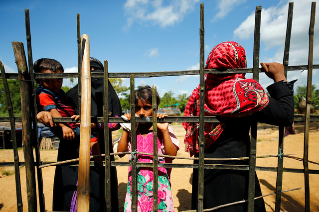 New Rohingya refugee people look on as they hold a fence near the Kutupalang makeshift refugee camp, in Cox's Bazar, Bangladesh, August 29, 2017. Credit:Reuters
