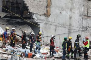 A member of rescue team (R) holds a megaphone next to his team mates as they search for survivors, in the rubble of a collapsed building, after an earthquake in Mexico City, Mexico September 25, 2017. Credit: Reuters/Nacho Doce