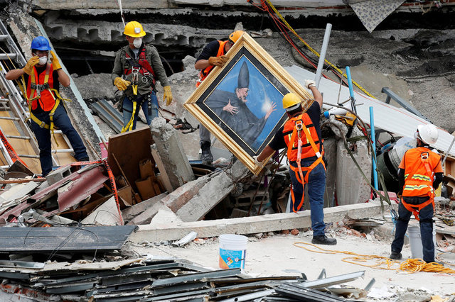Mexican and international rescue teams remove a painting as they search for survivors in a collapsed building after an earthquake, at Roma neighborhood in Mexico City, Mexico September 23, 2017. Credit: Reuters/Carlos Jasso
