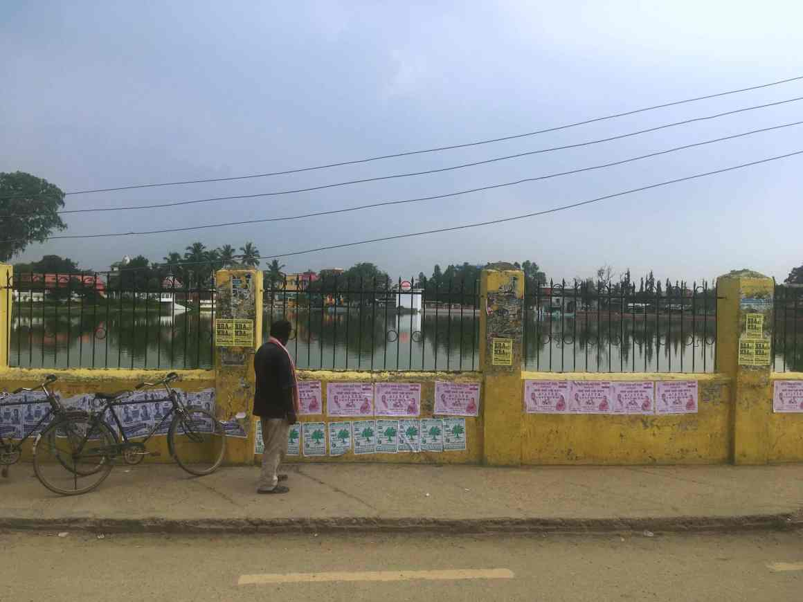 A man looks at election posters in front of Dhanus Sagar in Janakpur. Credit: Peter Gill