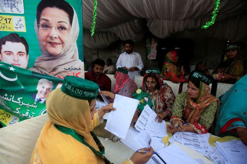 Workers of the PMLN political party guide voters and share voting lists outside a polling station in Lahore, Pakistan September 17, 2017. Credit:Reuters/Mohsin Raza
