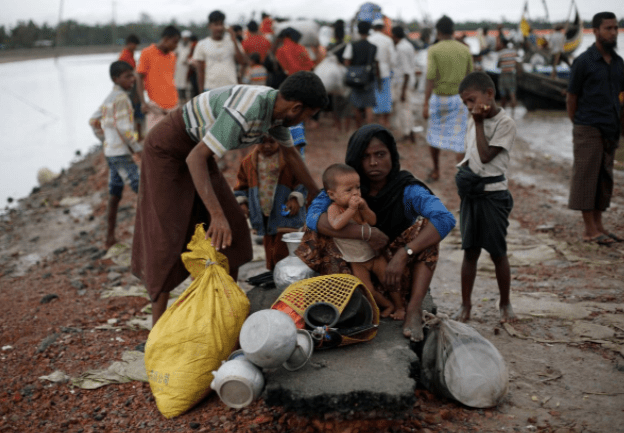 Rohingya refugees sit near a jetty after crossing the Bangladesh-Myanmar border. Credit: Reuters