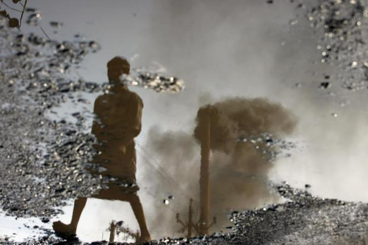 A chimney is reflected in a puddle polluted with chemicals at an industrial area of Surat November 25, 2009. Credit: Reuters/Arko Datta/Files
