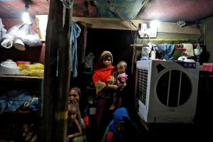 A family from the Rohingya community is pictured inside their shack at a camp in Delhi, Credit: Reuters
