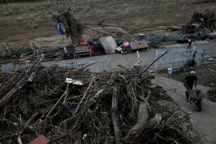 A woman looks for valuables among the damaged belongings on the street after the area was hit by Hurricane Maria in Toa Baja, Puerto Rico September 24, 2017. Credit: Reuters