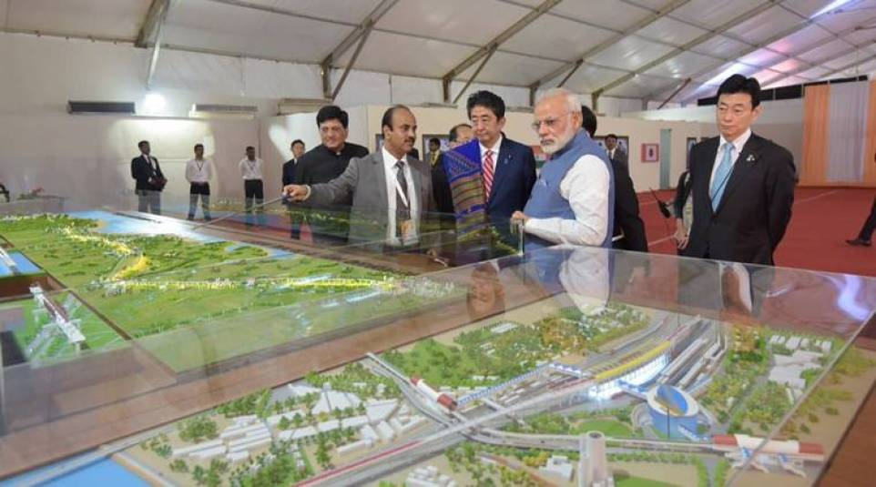 Prime Ministers Narendra Modi and Shinzo Abe look at a model of the bullet train. Credit: Twitter/@RailMinIndia