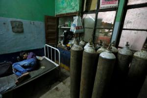 A man sleeps in a room containing oxygen tanks in the Baba Raghav Das hospital in Gorakhpur district, India August 13, 2017. Credit:Reuters