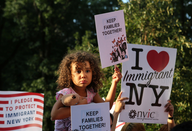 """A girl sitting on the shoulders of her father holds a sign reading """"Keep Families Together"""" at a protest against U.S. President Donald Trump's proposed end of the DACA program that protects immigrant children from deportation in New York City, U.S., August 30, 2017. Credit:Reuters"""