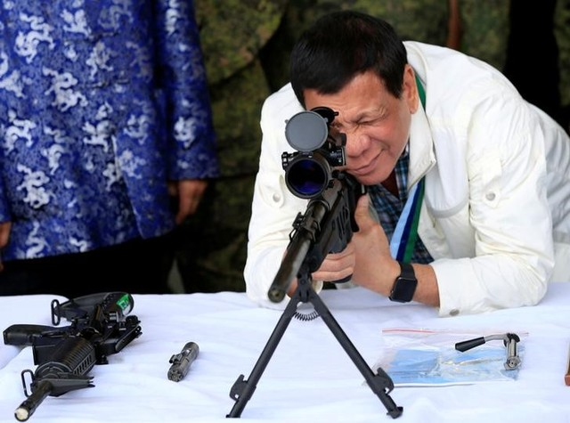 "Philippine President Rodrigo Duterte checks the scope of a 7.62mm sniper rifle during the turnover ceremony of China's urgent military assistance given ""gratis"" to the Philippines, at Clark Air Base, near Angeles City, Philippines June 28, 2017. Credit: Reuters"