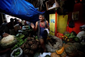 A vendor speaks to a customer at his stall at a wholesale fruit and vegetable market in Mumbai, India, August 14, 2017. Credit: Reuters