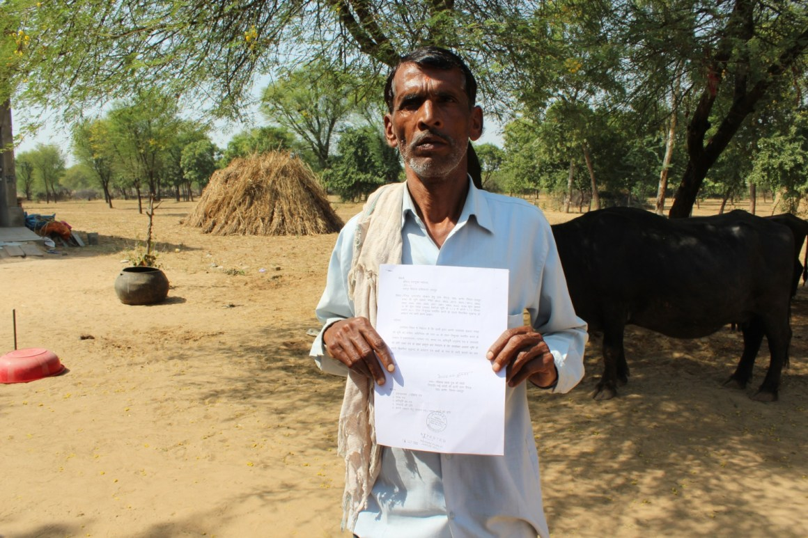 Gopal holding up the attested document of surrender