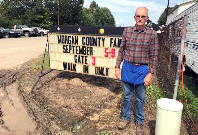 John Wilson, 70, stands next to a sign at the Morgan County Fair in McConnelsville, Ohio, U.S., September 6, 2017. Photo taken September 6, 2017. Credit: Reuters