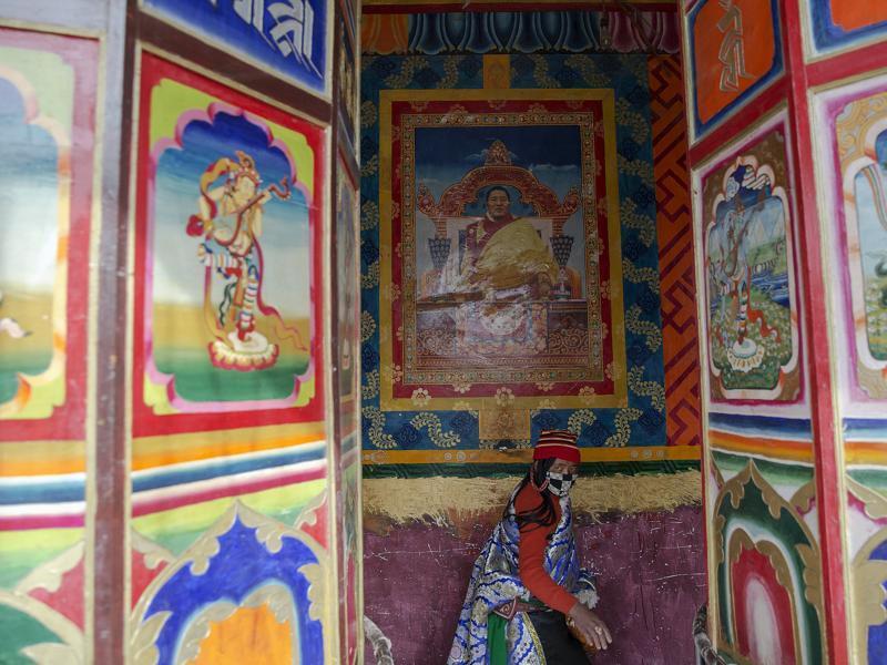 An ethnic Tibetan woman walks behind prayer wheels at the Larung Wuming Buddhist Institute. Credit: Reuters