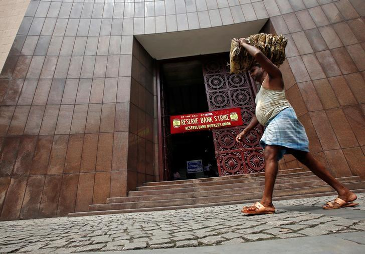 A labourer carrying dry leaves walks past a Reserve Bank of India (RBI) building during a nationwide strike in Kolkata, India September 2, 2016. Credit: Reuters/Rupak De Chowdhuri/File Photo