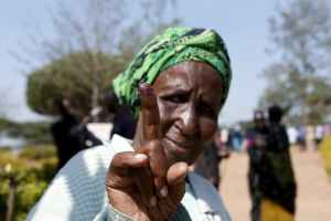 An elderly woman displays her inked finger after casting her vote during the 2016 presidential elections in Uganda. Credit: Reuters