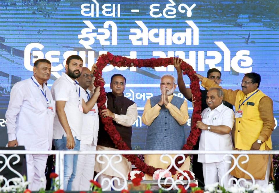 Prime Minister Narendra Modi being welcomed on stage at the public meeting in Ghogha in Gujarat on Sunday. Credit: PTI