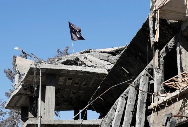 A flag of ISIS militants is pictured above a destroyed house near the Clock Square in Raqqa, Syria October 18, 2017. Picture taken October 18, 2017. Credit: Reuters