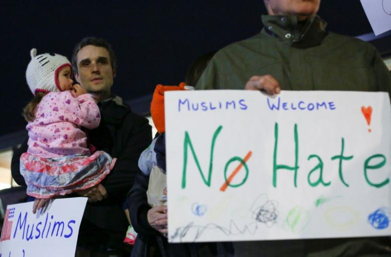 Demonstrators hold signs during a protest against President-elect Donald Trump and in support of Muslims residents in downtown Hamtramck, Michigan, U.S. on November 14, 2016. Credit: Reuters