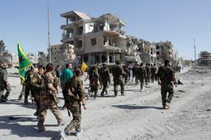 Fighters of Syrian Democratic Forces march along a road after Raqqa was liberated from the Islamic State militants, in Raqqa, Syria October 17, 2017. Credit: Reuters