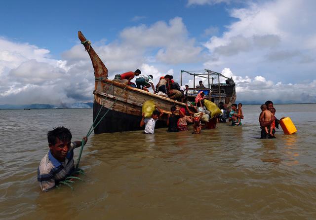 Rohingya refugees get off a boat after crossing the Bangladesh-Myanmar border through the Bay of Bengal in Shah Porir Dwip, Bangladesh September 11, 2017. Credit: Reuters