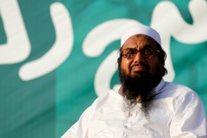 """FILE PHOTO - Hafiz Muhammad Saeed, chief of the banned Islamic charity Jamat-ud-Dawa, looks over the crowed as they end a """"Kashmir Caravan"""" from Lahore with a protest in Islamabad, Pakistan July 20, 2016. Credit: Reuters"""