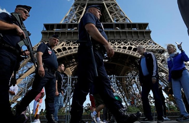 French CRS policemen patrol as tourists walk past in front of the Eiffel Tower in Paris, France August 20, 2016. Credit: Reuters/Pascal Rossignol/File Photo