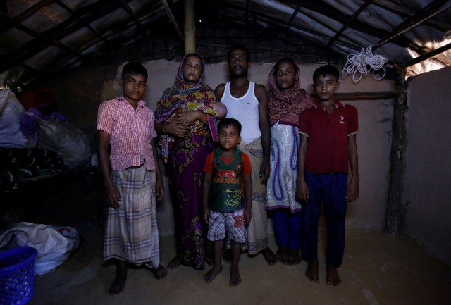 Mohammad Zubair (L), 14, a Rohingya refugee boy, poses for a picture along with his mother Fatima Begum (2nd L), Father Nur Kobir (3rd R), sister Anu Ara (2nd R), brother Mohammad Harris (R) and brother Mohammad Zasangir (C) inside their temporary shelter at Kutupalong refugee camp near Cox's Bazar, Bangladesh, November 12, 2017. Credit: Reuters/Navesh Chitrakar
