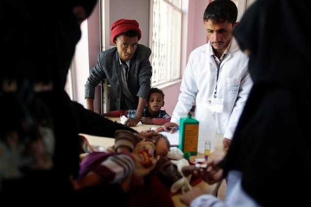 A man and his son look as another son is being treated at a malnutrition treatment center in Sanaa, Yemen November 4, 2017. Credit: Reuters/Khaled Abdullah
