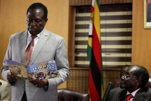 FILE PHOTO: Zimbabwe's President Robert Mugabe looks on as his deputy Emmerson Mnangagwa reads a card during Mugabe's 93rd birthday celebrations in Harare, Zimbabwe, February 21, 2017. Credit: Reuters/Philimon Bulawayo/File Photo