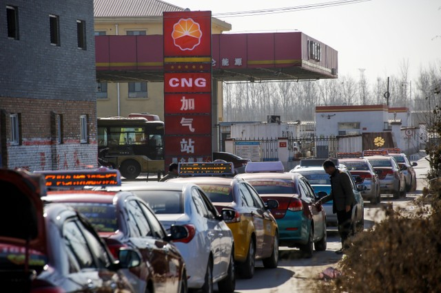 Cars line up at a filling station for liquid natural gas (LNG), one of a few that is open for business, in Baoding, Hebei province, China, December 5, 2017. Credit: Reuters/Thomas Peter