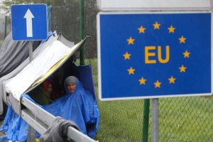 An EU sign is seen as migrants wait in the no man's land to cross the border to Slovenia from Trnovec, Croatia, October 19, 2015. Credit: Reuters/Srdjan Zivulovic