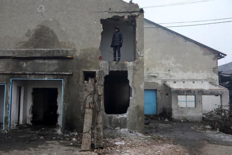 A migrant stands outside a derelict customs warehouse in Belgrade, Serbia, December 22, 2016. Credit: Reuters/Marko Djurica