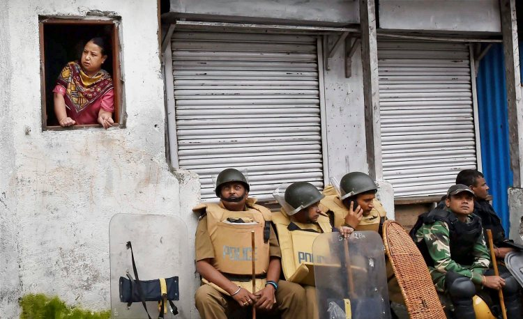 Darjeeling: Security personnel guard sit as woman looks out of window in Darjeeling on Sunday. PTI Photo by Ashok Bhaumik(PTI6_18_2017_000150B)