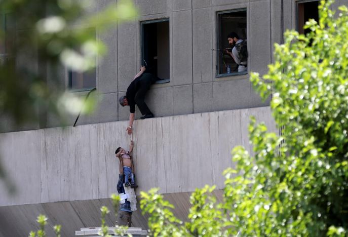 A boy is evacuated during an attack on the Iranian parliament in central Tehran, Iran, June 7, 2017. Omid Vahabzadeh/TIMA via REUTERS