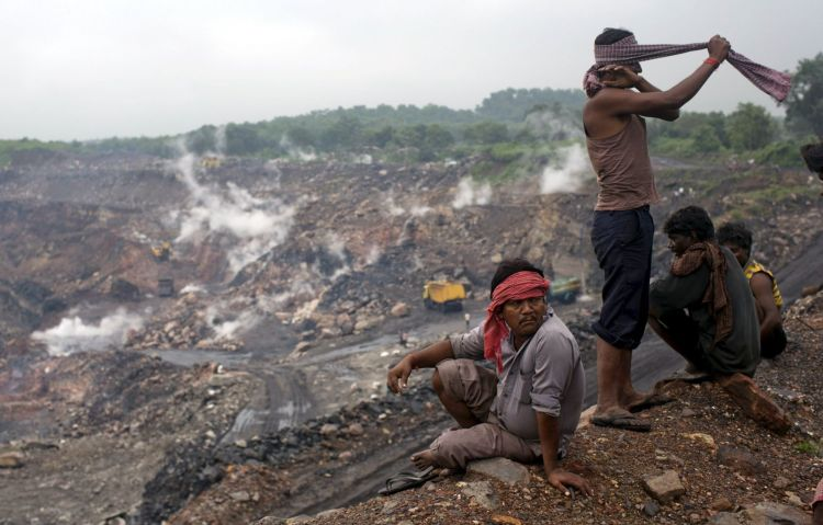 Workers sit atop an open cast coal field at Dhanbad district in Jharkhand, India, in this September 18, 2012 file photo. Photo Reuters